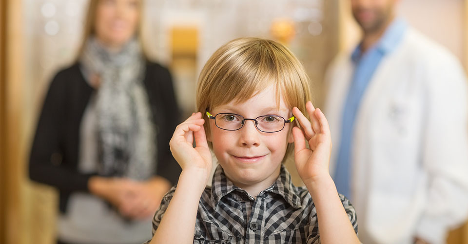 smiling boy trying glasses with optometrist and mother standing in background at store